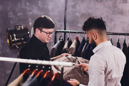 Male customer at shopping mall trying business clothes, shop assistant helping to client.