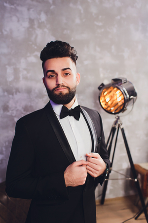 Portrait of handsome stylish man in elegant black suit.