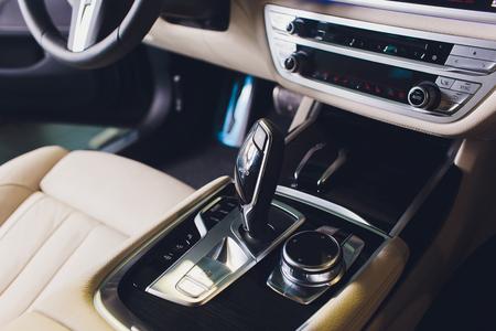 Coche de lujo en el interior. Interior de coche moderno de prestigio. Asientos delanteros con volante. Cabina blanca. Foto de archivo