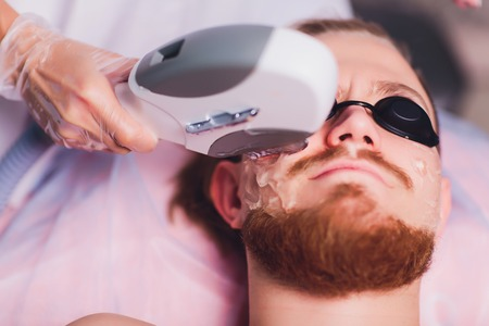 Young Man Receiving Laser Hair Removal Treatment At Beauty Center. 版權商用圖片