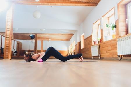 Sporty beautiful young woman practicing yoga, working out, doing easy alternative to Chaturanga Dandasana, half push-up, Eight-Limbed or Caterpillar pose, Ashtanga Namaskara, studio. Imagens