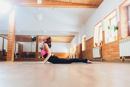 Young yogi attractive woman practicing yoga concept, stretching in Cobra exercise, Bhujangasana pose, working out, wearing sportswear, black tank top and pants, full length, loft background.