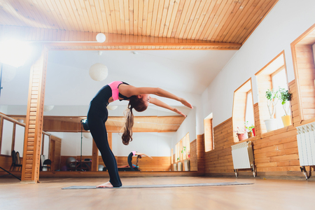 the girl athlete keeps the hands at the breast, Namaste, yoga.