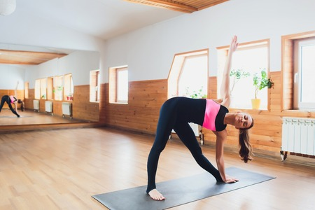 Young attractive woman practicing yoga, standing in Revolved Triangle exercise, Parivrrta Trikonasana pose, working out wearing sportswear, indoor full length, isolated against studio background.