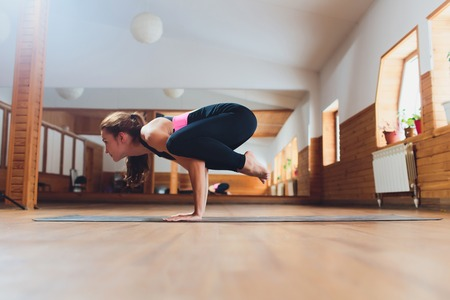 Young attractive yogi woman practicing yoga, standing in Parsva Bakasana exercise, Side Crane pose, working out, wearing black sportswear, cool urban style, full length, studio background.
