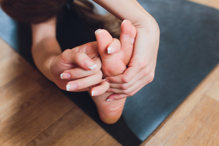 Close-up of a girl doing an asana bending forward with her hands towards her legs. Sitting on the floor on a pink yoga mat. Grip on foots. Marma points.