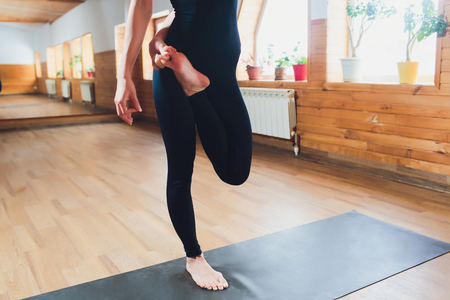 Portrait of sporty beautiful blond young woman in sportswear working out indoors, doing balance back bend, Natarajasana, Lord of the Dance posture, variation with belt on mat, full length. Reklamní fotografie - 120790995
