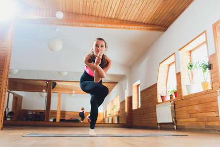 Young attractive woman practicing yoga, standing in Eagle exercise, Garudasana pose, working out, wearing sportswear, suit, indoor full length, studio background. 写真素材