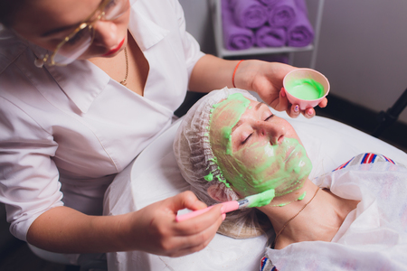 cosmetologist with the help of a special make-up brush makes a therapeutic spa mask from green algae against aging of a young woman.