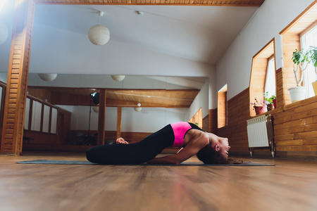 Young yogi attractive woman practicing yoga concept, standing in salamba sirsasana exercise, headstand pose, working out, wearing sportswear, black tank top and pants, full length, loft background. Advanced Fish pose Foto de archivo