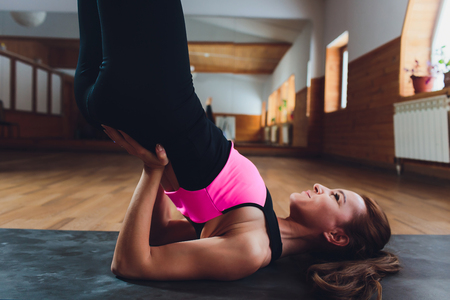 Young sporty attractive woman practicing yoga, doing Salamba Sarvangasana exercise, supported Shoulder stand pose, working out, wearing sportswear, grey pants, top, indoor full length, at yoga studio.