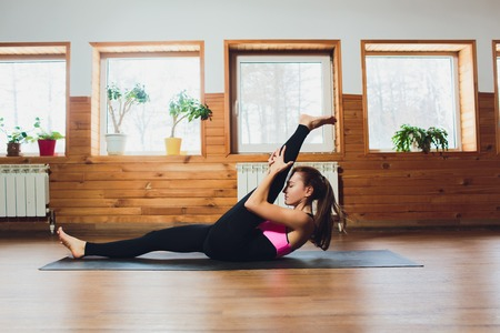 Young yogi sporty woman working out, warming up using yogic belt, lying in yoga Supta Padangushthasana, One Leg Lift exercise, reclined variation of Extended Hand to Big Toe pose, studio, side view. Stock Photo