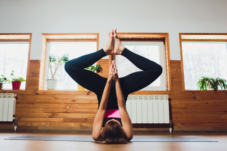 Young sporty woman practicing yoga, doing Alternate Nostril Breathing exercise, nadi shodhana pranayama pose, working out, wearing sportswear, grey top, indoor close up, white yoga studio.