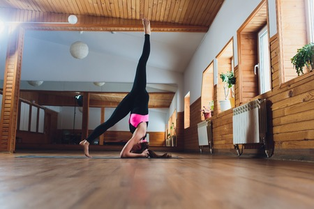 Young yogi attractive woman practicing yoga concept, standing in salamba sirsasana exercise, headstand pose, working out, wearing sportswear, black tank top and pants, full length, loft background. Foto de archivo