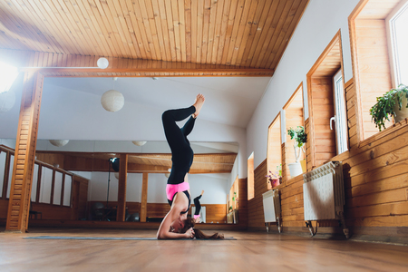Young yogi attractive woman practicing yoga concept, standing in salamba sirsasana exercise, headstand pose, working out, wearing sportswear, black tank top and pants, full length, loft background. 版權商用圖片