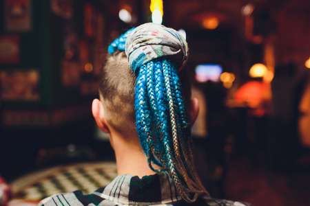 Fashion of hairstyle cornrows braid : many small braids tail of creative hairstyle with thick plaits, pigtails as African braid, head with braids from material in pink on dreadlocks hair.
