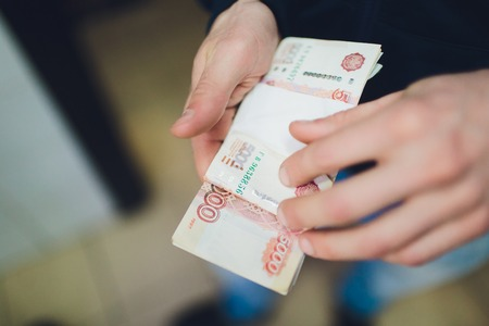 man giving money, Russian Ruble banknotes, over his desk in a dark office - bribery and corruption concept.russian rubles banknotes. Financial theme.stack of banknotes in a mans hand.