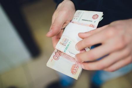 Mann, der Geld, russische Rubel-Banknoten, über seinem Schreibtisch in einem dunklen Büro gibt - Bestechungs- und Korruptionskonzept.Russische Rubel-Banknoten. Finanzthema. Stapel von Banknoten in der Hand eines Mannes.
