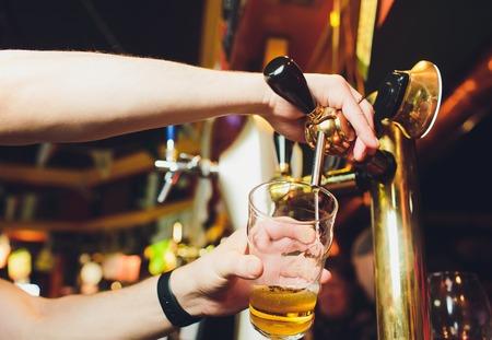 Wir treffen uns oktoberfest. Hand des Barkeepers, der ein großes Lagerbier in den Hahn gießt. Gießen von Bier für den Kunden. Seitenansicht des jungen Barkeepers, der Bier gießt, während er an der Bartheke steht.