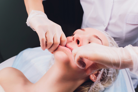 cosmetologist makes a buccal massage of the patients facial muscles. 写真素材 - 120897410