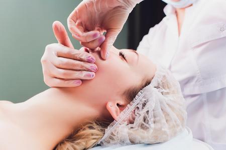 Kosmetikerin macht eine bukkale Massage der Gesichtsmuskeln des Patienten. Standard-Bild