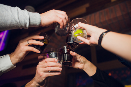 Hands of people with glasses of whiskey or wine, celebrating and toasting in honor of the wedding or other celebration. Banque d'images