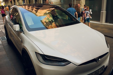 BARCELONA, SPAIN - August 25, 2018: White Tesla model X is charging in the parking lot. luxury crossover utility vehicle made by Tesla.