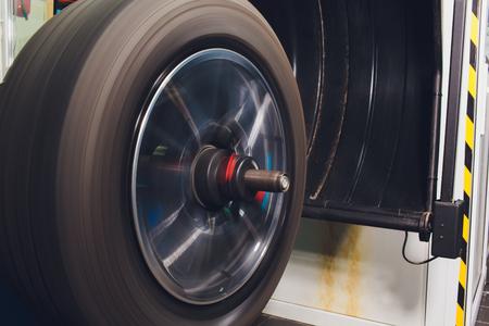 El reparador equilibra la rueda e instala el neumático sin cámara del automóvil en el equilibrador en el taller.