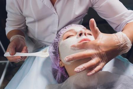 Beautiful european woman having facial skin procedure by applying a white rejuvenation mask by cosmetologist. Banco de Imagens
