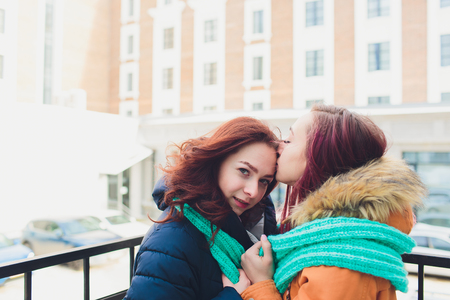 lesbian Couple of young women. Girl wears warm hat girl closes friends ears with her hands in mittens in cold winter.
