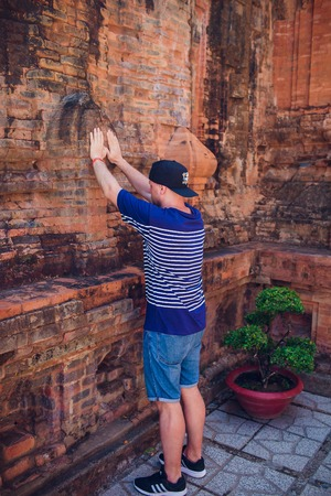 the young man prays against the wall of the temple. concept of modern religion.
