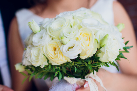the bride is holding a bouquet of the bride from white roses and eustoma. Imagens