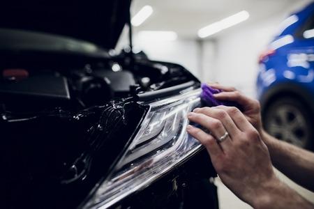 Worker hands installs car paint protection film wrap headlamp