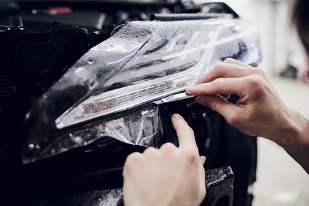Worker hands installs car paint protection film wrap auto headlight 版權商用圖片