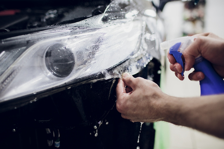 Worker hands installs car paint protection film wrap auto headlight Stock Photo