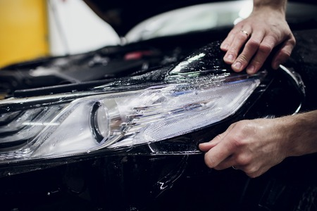 Worker hands installs car paint protection film wrap auto headlight