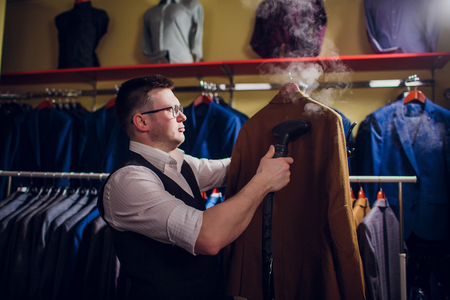 tailor cuts and sews a suit. A young man in the tailoring shop makes mens clothing. Custom-made clothing workshop. holds in her hand an electric iron. wet-heat treatment