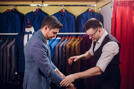 Businessman in classic vest against row suits in shop. Man helps another try on suit in clothing store