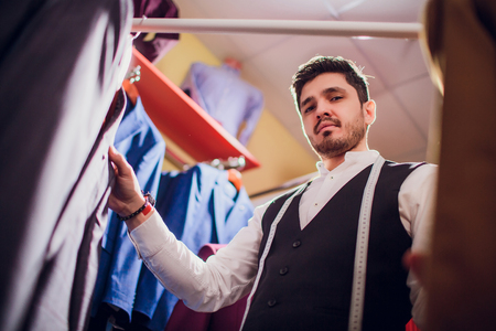 Over shoulder view bearded fashion designer fitting bespoke suit to model, close-up shot