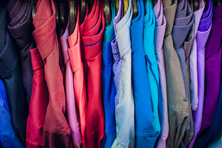 Big clothing store, many rows with hangers with pants and t-shirts, variety sizes Banco de Imagens