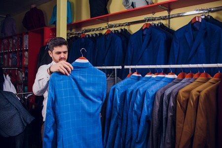 Tailor, tailoring. Mens suit, tailor in his workshop. Elegant mans suits hanging in row. Luxury mens classic suits on rack in elegant mens boutique.