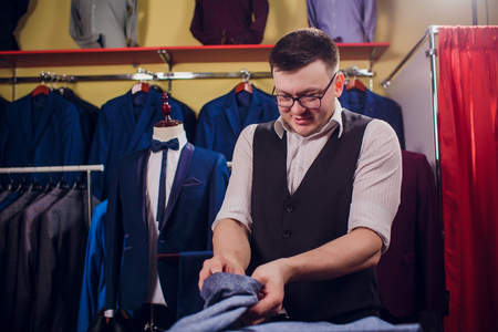 Tailor, tailoring. Mens suit, tailor in his workshop. Elegant mans suits hanging in row. Luxury mens classic suits on rack in elegant mens boutique. yawns tired choosing Stockfoto