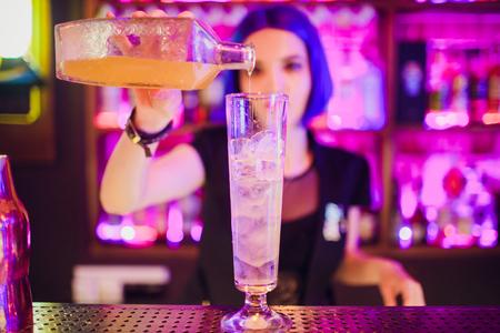 Barkeeper-Hand, die ein Glas mit leicht saurem Sommercocktail mit rosa Pfirsichlikör hält, der mit Blumen unter der Bartheke verziert ist