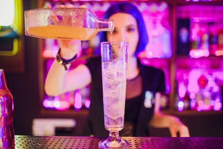 Bartender hand holding a glass with summer light sour cocktail with pink peach liquor decorated with flower under the bar counter