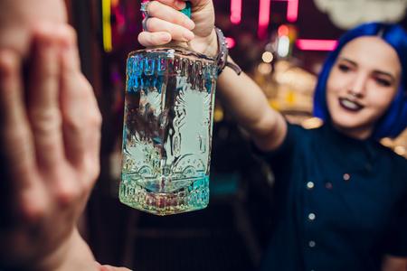 Schönes fröhliches brünettes Barkeeper-Mädchen in weißem Hemd und schwarzer Fliege, serviert Alkoholgetränk in der Nachtclub-Bar, hält Flasche in der Hand, gießt Getränk in Glas