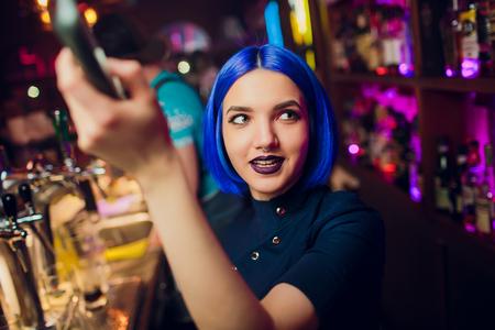 Hermosa chica morena alegre bartender en camisa blanca y pajarita negra, sirviendo bebida alcohólica en el bar de la discoteca, sosteniendo la botella en la mano, vertiendo bebida en vidrio