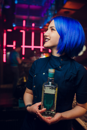 Beautiful cheerful brunette bartender girl in white shirt and black bow tie, serving alcohol drink at nightclub bar, holding bottle in hand, pouring drink in glass