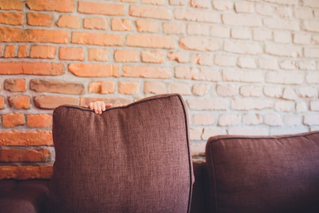 a small child hid behind a pillow on the couch. Stock Photo