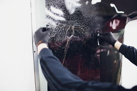 Applying tinting foil on car window in garage