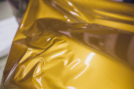Car wrapping specialist putting vinyl foil or film on car wrapping protective film yacht, boat, ship, car, mobile home. yellow gold film hand pulls